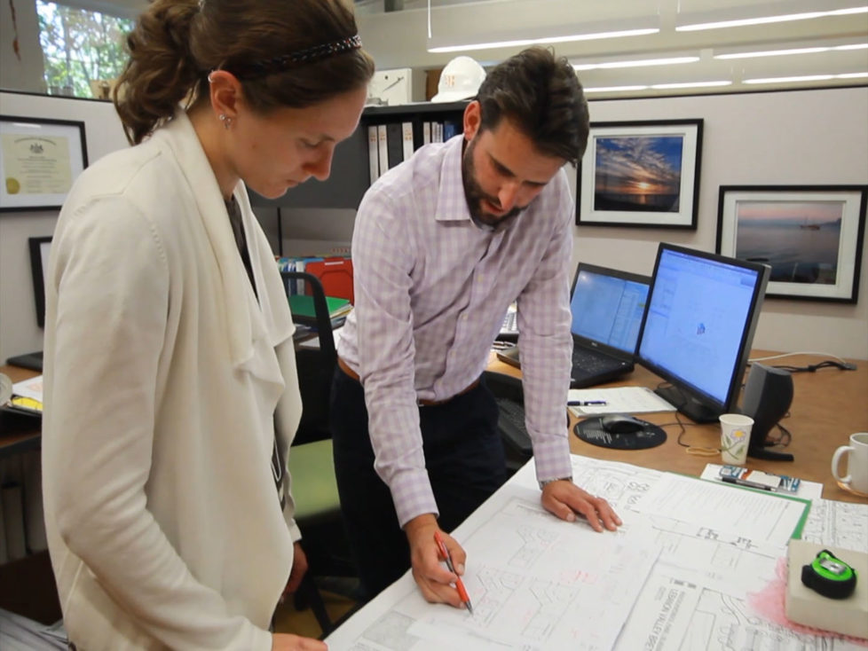 Peter Kerekgyarto, RA and Principal at Beers + Hoffman Architecture pointing to a plan on his desk and discussing with Sarah Faus CAD Designer